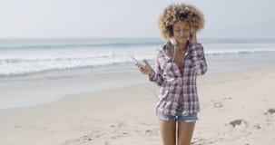 Νέα γυναίκα που ακούει τη μουσική στην παραλία Στοκ Φωτογραφίες