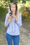 Νέα γυναίκα που ακούει τη μουσική στο έξυπνο τηλέφωνο υπαίθρια Στοκ Φωτογραφίες