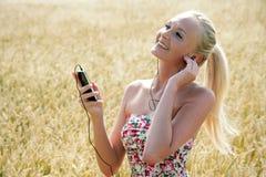 Νέα γυναίκα που ακούει τη μουσική Στοκ Εικόνες