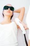 Νέα γυναίκα που λαμβάνει την επεξεργασία λέιζερ epilation Στοκ εικόνα με δικαίωμα ελεύθερης χρήσης