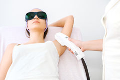 Νέα γυναίκα που λαμβάνει την επεξεργασία λέιζερ epilation Στοκ Φωτογραφία