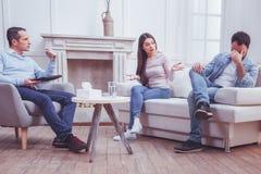 Νέα γυναίκα που ανακαλύπτει τους συζύγους της κατά τη διάρκεια της ψυχιατρικής συμμετοχής στοκ εικόνες