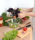 Νέα γυναίκα που αναμιγνύει τη φρέσκια σαλάτα στην κουζίνα Στοκ Φωτογραφία