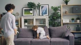 Νέα γυναίκα που απολαμβάνει την πάλη μαξιλαριών με το μικρό παιδί που ρίχνει τα μαξιλάρια στον καναπέ απόθεμα βίντεο