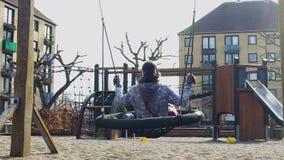 Νέα γυναίκα που απολαμβάνει την υπαίθρια ταλάντευση στο πάρκο, μνήμες παιδικής ηλικίας, μοναξιά απόθεμα βίντεο