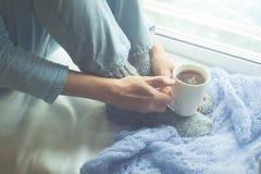Νέα γυναίκα που απολαμβάνει τον καφέ ή το τσάι πρωινού της, που φαίνεται έξω το παράθυρο Όμορφο ρομαντικό unrecognizable κορίτσι  στοκ φωτογραφία με δικαίωμα ελεύθερης χρήσης
