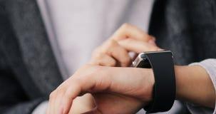 Νέα γυναίκα που αποτελεί τις χειρονομίες στη φορετή συσκευή υπολογιστών smartwatch της, έξυπνα χέρια ρολογιών κοντά 4k φιλμ μικρού μήκους