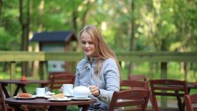 Νέα γυναίκα που απολαμβάνει ένα δοχείο του τσαγιού φιλμ μικρού μήκους