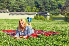 Νέα γυναίκα που απολαμβάνει μια ανάγνωση βιβλίων υπαίθρια Στοκ Φωτογραφίες