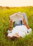 Νέα γυναίκα που απολαμβάνει την ανάγνωση βιβλίων υπαίθρια Στοκ Φωτογραφίες