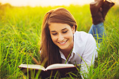 Νέα γυναίκα που απολαμβάνει την ανάγνωση βιβλίων υπαίθρια Στοκ φωτογραφία με δικαίωμα ελεύθερης χρήσης