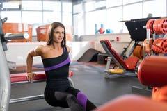 Νέα γυναίκα που ασκεί στον πάγκο στη γυμναστική στοκ εικόνες