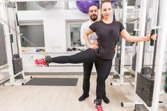 Νέα γυναίκα που ασκεί τα πόδια με τον προσωπικό εκπαιδευτή Στοκ Εικόνα