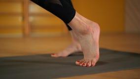 Νέα γυναίκα που ασκεί τεντώνοντας τα πόδια, την ικανότητα ή τη γιόγκα μόνο στο χαλί Unrecognizable κορίτσι στο μαύρο κομπινεζόν Υ απόθεμα βίντεο