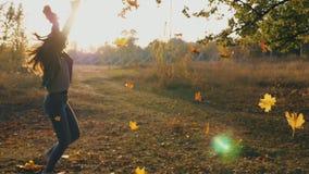 Νέα γυναίκα που αυξάνει τα χέρια της και που περιστρέφει γύρω από τα διασκορπίζοντας φύλλα φθινοπώρου Ευτυχές κορίτσι που παρουσι απόθεμα βίντεο