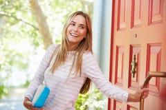 Νέα γυναίκα που αφήνει το σπίτι για την εργασία με το συσκευασμένο μεσημεριανό γεύμα στοκ εικόνα