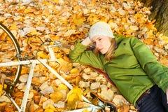 Νέα γυναίκα που βάζει στα φύλλα φθινοπώρου στοκ εικόνα με δικαίωμα ελεύθερης χρήσης