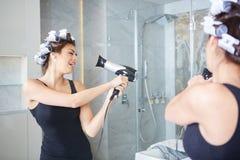Νέα γυναίκα που βάζει τα ρόλερ στην τρίχα της, λουτρό στοκ εικόνες