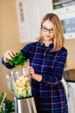 Νέα γυναίκα που βάζει τα φρούτα και λαχανικά στο eletrical μπλέντερ στοκ φωτογραφία