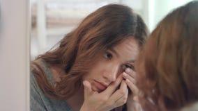 Νέα γυναίκα που βάζει το φακό επαφής για τον μπροστινό καθρέφτη λουτρών ματιών στο σπίτι φιλμ μικρού μήκους