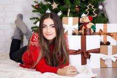 Νέα γυναίκα που βρίσκεται κοντά στο διακοσμημένο χριστουγεννιάτικο δέντρο Στοκ Φωτογραφίες