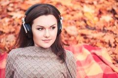 Νέα γυναίκα που βρίσκεται σε μια κουβέρτα σε ένα πάρκο φθινοπώρου και που ακούει το θόριο Στοκ Εικόνες