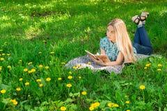 Νέα γυναίκα που βρίσκεται, που σκέφτεται και που γράφει στο ημερολόγιό της στη χλόη με τα λουλούδια Μπροστινή όψη Στοκ Φωτογραφίες