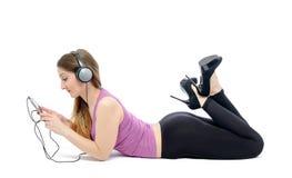 Νέα γυναίκα που βρίσκεται στα ακουστικά στο λευκό Στοκ Φωτογραφίες