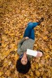 Νέα γυναίκα που βρίσκεται στα ξηρά φύλλα σε ένα πάρκο φθινοπώρου Στοκ εικόνα με δικαίωμα ελεύθερης χρήσης
