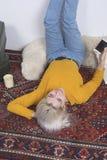 Νέα γυναίκα που βρίσκεται στην πλάτη που κρατά στο σπίτι ένα τηλέφωνο Στοκ φωτογραφία με δικαίωμα ελεύθερης χρήσης