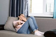 Νέα γυναίκα που βρίσκεται στον καναπέ με έναν τηλεχειρισμό από τη TV και τα χασμουρητά από την πλήξη Στοκ Εικόνα