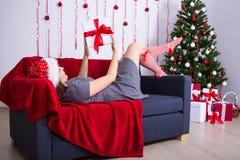 Νέα γυναίκα που βρίσκεται στον καναπέ με το διακοσμημένο χριστουγεννιάτικο δέντρο στο σπίτι Στοκ εικόνα με δικαίωμα ελεύθερης χρήσης