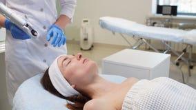 Νέα γυναίκα που βρίσκεται στο κρεβάτι και που έχει του προσώπου mesotherapy σε ένα σαλόνι ομορφιάς απόθεμα βίντεο