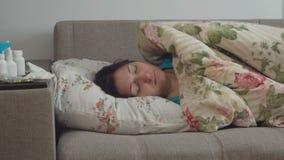 Νέα γυναίκα που βρίσκεται στο κρεβάτι που τυλίγεται σε ένα κάλυμμα απόθεμα βίντεο