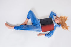 Νέα γυναίκα που βρίσκεται στο πάτωμα στις πυτζάμες του με ένα lap-top Στοκ φωτογραφία με δικαίωμα ελεύθερης χρήσης