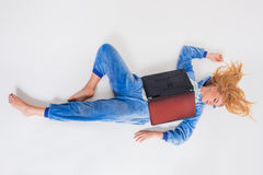 Νέα γυναίκα που βρίσκεται στο πάτωμα στις πυτζάμες του με ένα lap-top Στοκ Εικόνες