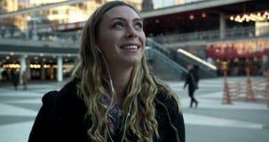 Νέα γυναίκα που γελά και που χαμογελά μιλώντας στο τηλέφωνο στην κεντρική Στοκχόλμη απόθεμα βίντεο
