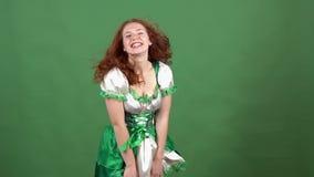 Νέα γυναίκα που γιορτάζει την ημέρα Αγίου Πάτρικ ` s στον πράσινο τοίχο που φορά τον παραδοσιακό θυελλώδη καιρό φορεμάτων απόθεμα βίντεο