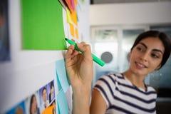 Νέα γυναίκα που γράφει στην κολλώδη σημείωση στο γραφείο Στοκ Φωτογραφίες