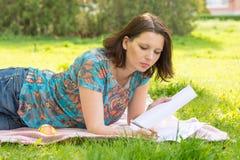 Νέα γυναίκα που γράφει στις αλεπούδες της Λευκής Βίβλου που βρίσκονται σε ένα λιβάδι στο πάρκο Στοκ Εικόνες