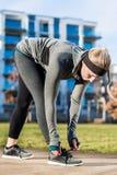 Νέα γυναίκα που δένει τα κορδόνια των παπουτσιών της φορώντας την τάση Στοκ Εικόνες