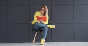 Νέα γυναίκα που διαβάζει ένα βιβλίο απόθεμα βίντεο