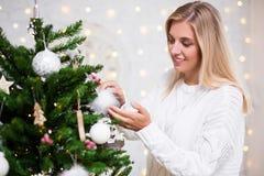 Νέα γυναίκα που διακοσμεί το χριστουγεννιάτικο δέντρο στο σπίτι στοκ εικόνα
