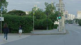 Νέα γυναίκα που διασχίζει μια οδό στην πόλη την ηλιόλουστη θερινή ημέρα απόθεμα βίντεο