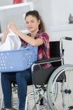 Νέα γυναίκα που διπλώνει τα ενδύματα από την αναπηρική καρέκλα Στοκ Εικόνες
