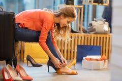Νέα γυναίκα που δοκιμάζει τα σανδάλια στο κατάστημα παπουτσιών Στοκ Εικόνα