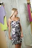 Νέα γυναίκα που δοκιμάζει το φόρεμα επάνω Στοκ Φωτογραφίες