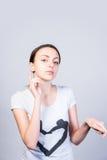 Νέα γυναίκα που δείχνει πάνω-κάτω ενάντια σε γκρίζο Στοκ φωτογραφία με δικαίωμα ελεύθερης χρήσης