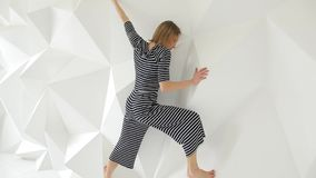 Νέα γυναίκα που εκτελεί τις σύγχρονες κινήσεις χορού στο άσπρο στούντιο φιλμ μικρού μήκους