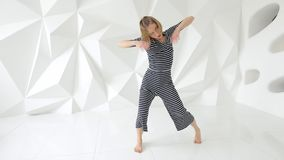 Νέα γυναίκα που εκτελεί τις σύγχρονες κινήσεις χορού στο άσπρο στούντιο απόθεμα βίντεο